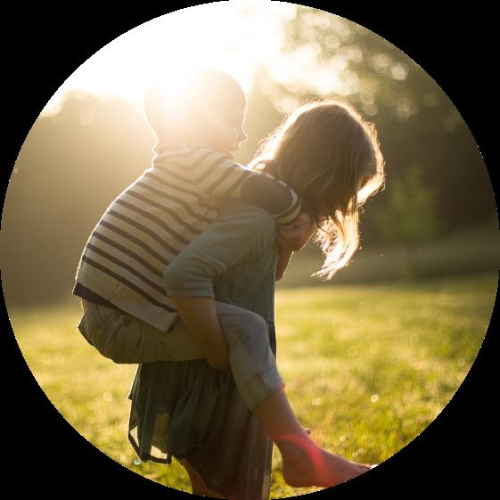 Foto com borda arredondada de um adulto, de perfil, segurando uma criança nas costas, de cavalinho, com os braços envoltos nas pernas da criança. A criança segura o pescoço do adulto com os braços. Ao fundo, há uma paisagem verde, com grama e árvores, desfocados. A foto foi tirada contra a luz do sol.
